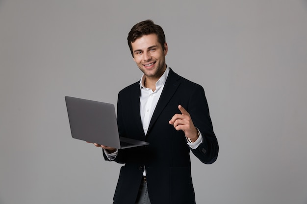 Imagen del apuesto hombre de negocios de 30 años en traje de regocijo mientras usa la computadora portátil, aislado sobre pared gris
