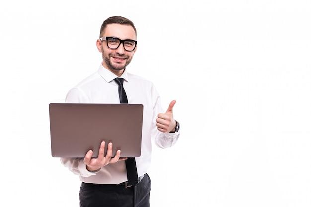 Imagen del apuesto joven barbudo sosteniendo un portátil mostrando los pulgares para arriba sobre una pared blanca aislada de fondo