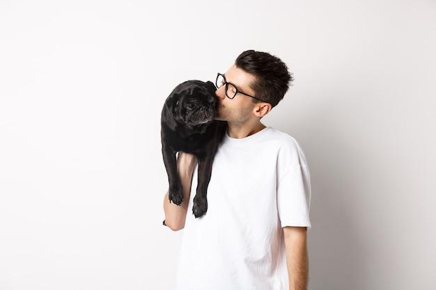 Imagen del apuesto joven besando a su lindo pug negro, sosteniendo el perro en el hombro, de pie sobre fondo blanco.