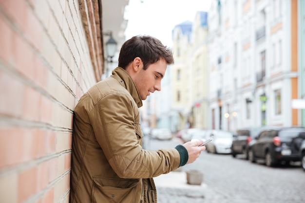 Imagen de apuesto joven caminando por la calle y charlando con su teléfono al aire libre