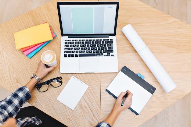 Imagen de arriba de cosas de trabajo en la mesa. manos de mujer joven que trabaja con la computadora portátil, sosteniendo una taza de café. cuadernos, gafas negras, trabajo duro, éxito, diseño gráfico.