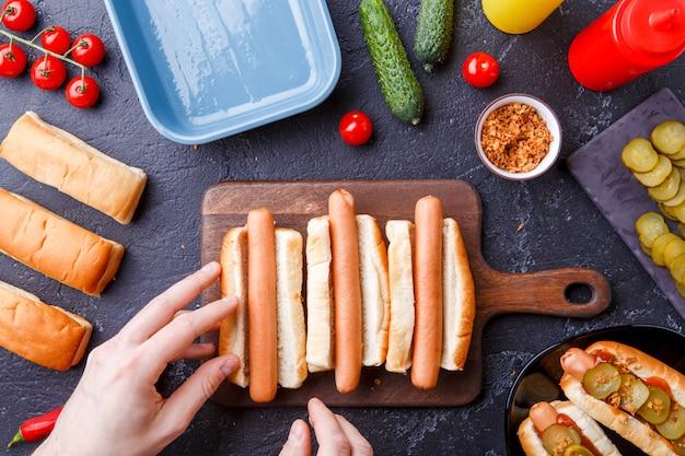 Imagen desde arriba del hombre haciendo perritos calientes en la tabla de cortar en la mesa con salchichas