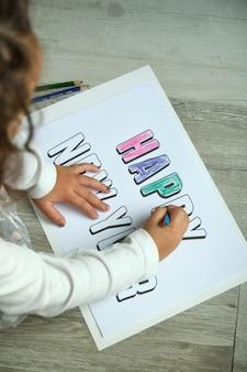 Imagen desde arriba de una niña irreconocible coloreando letras de feliz año nuevo con lápices de colores