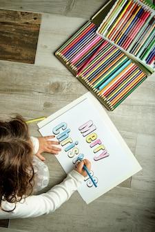 Imagen de arriba de una niña irreconocible coloreando letras de feliz navidad con lápices de colores