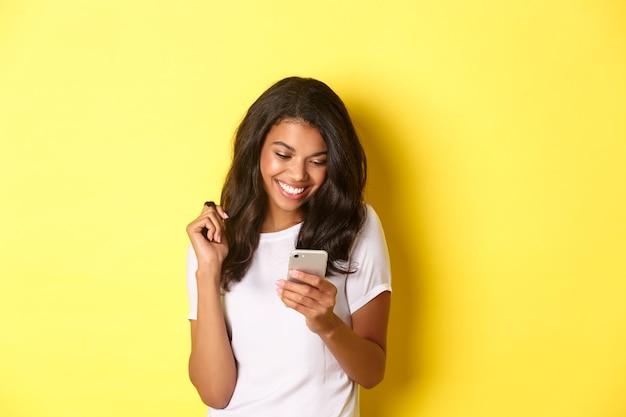 Imagen de atractiva chica afroamericana en mensajería de camiseta blanca en smartphone mirando móvil