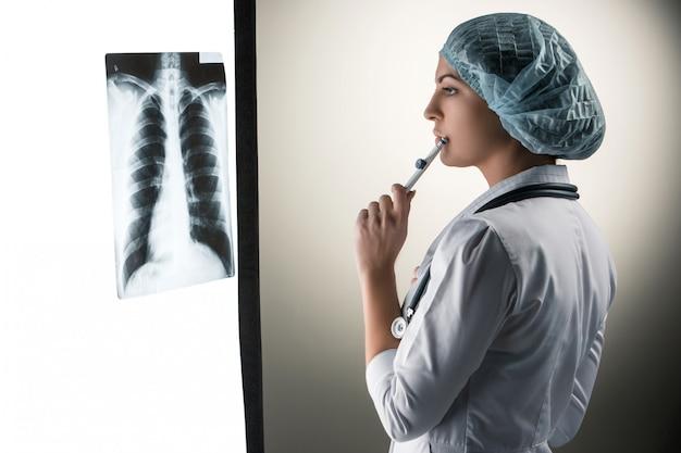 Imagen de atractiva doctora mirando resultados de rayos x