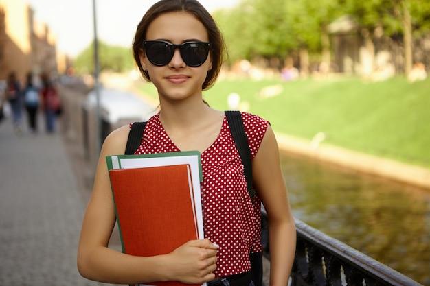 Imagen de una atractiva estudiante de moda con elegantes gafas de sol y un vestido rojo de lunares sosteniendo cuadernos, descansando durante las vacaciones en el campus universitario, posando al aire libre