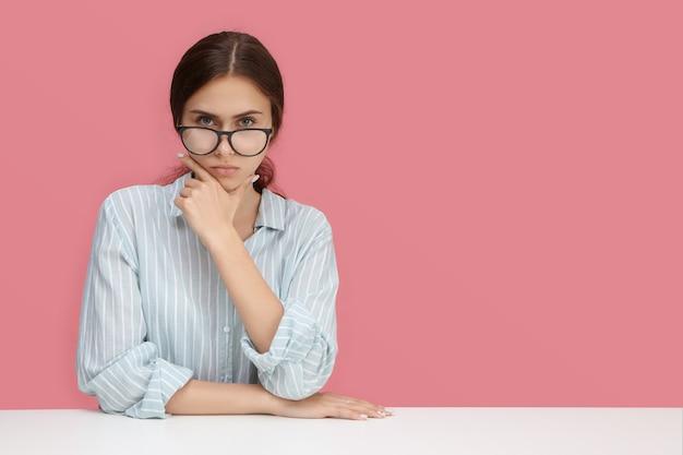 Imagen de atractiva joven empleada confiada con elegantes anteojos y camisa formal con expresión seria o estricta, tocando su rostro, pensando en el trabajo