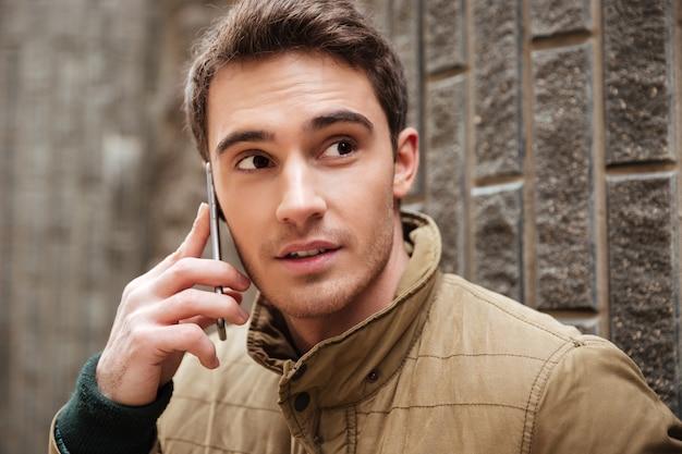 Imagen de atractivo joven caminando por la calle y mirando a un lado mientras habla por su teléfono.