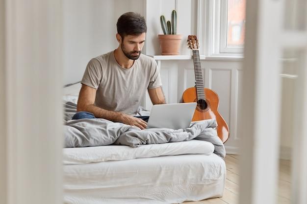 Imagen de un atractivo joven que se sienta en una cama cómoda, sincroniza archivos multimedia en una computadora portátil, trabaja como autónomo desde casa, disfruta del tiempo libre viendo películas, descansa en un apartamento acogedor.