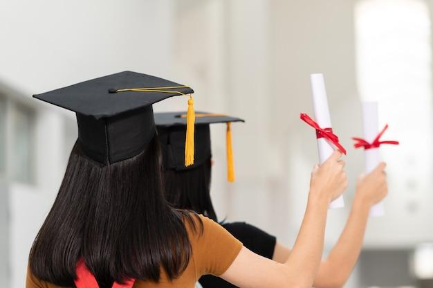 La imagen de atrás de una estudiante universitaria graduada con un sombrero negro borla amarilla