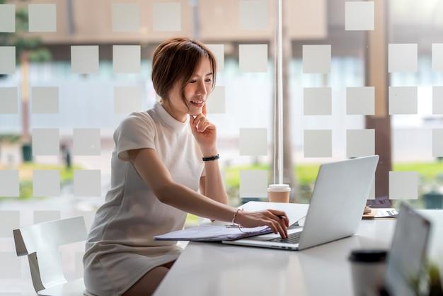 Imagen de una bella mujer asiática trabajando en una tableta y documentos en una oficina moderna.
