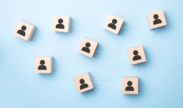 Imagen de bloques de madera con icono de personas sobre mesa de menta, construyendo un equipo fuerte, recursos humanos y concepto de gestión