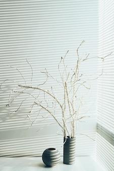 Imagen de bodegón de madera muerta de pie en un jarrón junto a la ventana cerrada de su casa