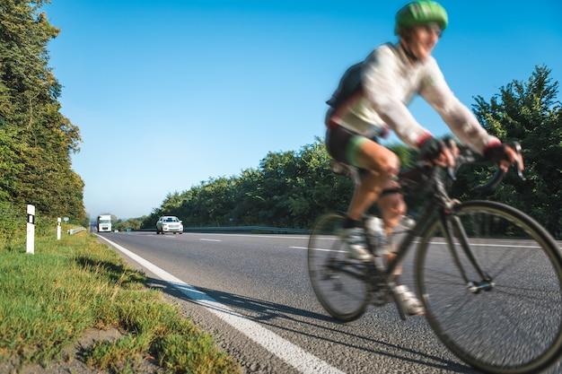 Imagen borrosa de ciclistas atletas corriendo a alta velocidad en la carretera