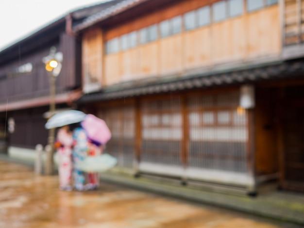 Imagen borrosa de mujeres vestidas con kimonos japoneses tradicionales en la zona del casco antiguo que es única y conservada en takayama, japón