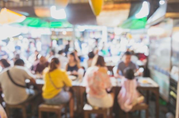 Imagen borrosa de personas sentadas alrededor de la mesa en la tienda local de comida callejera asiática