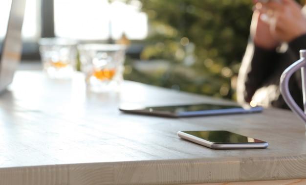Imagen borrosa del teléfono inteligente en la mesa