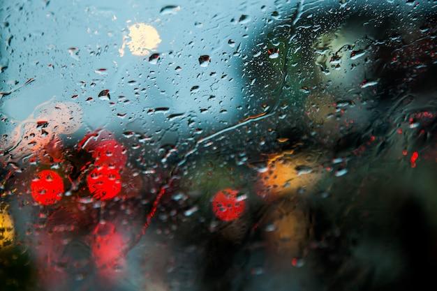 Imagen borrosa de la vista de tráfico a través del parabrisas de un coche cubierto de lluvia