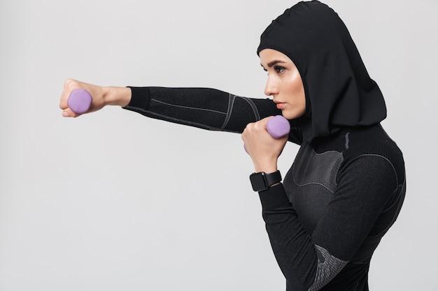 Imagen del boxeador de combate musulmán de fitness mujer joven posando aislado hacer ejercicios con pesas.