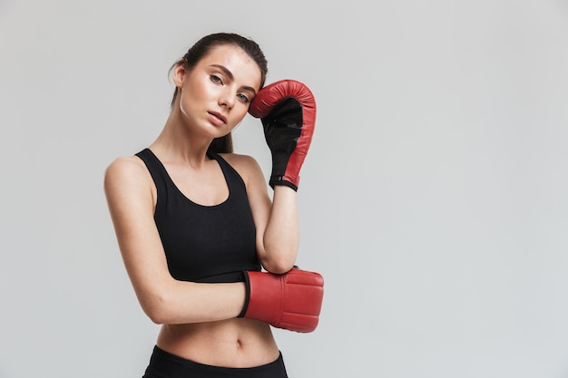 Imagen de un boxeador de mujer de fitness deporte joven y bella aislado sobre pared gris hacer ejercicios en guantes.