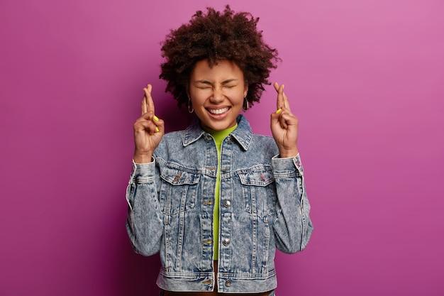 Imagen brillante de una mujer exagerada feliz con peinado rizado, cruza los dedos para la buena suerte, cree en que suceda algo agradable, reza para que mejore, mantiene los ojos cerrados, aislado sobre una pared púrpura