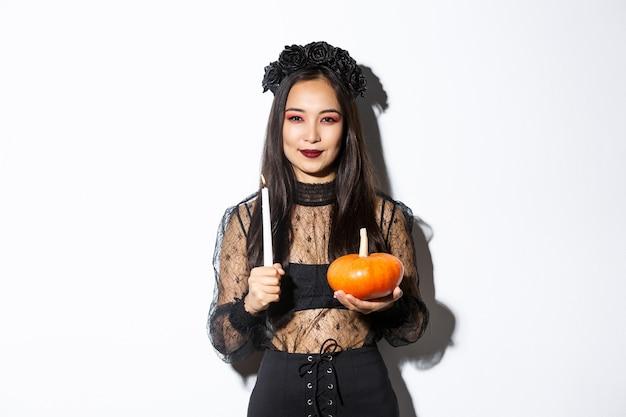 Imagen de bruja asiática sonriente astuta en traje gótico, sosteniendo una vela con calabaza y mirando a la cámara astucia, de pie sobre fondo blanco.