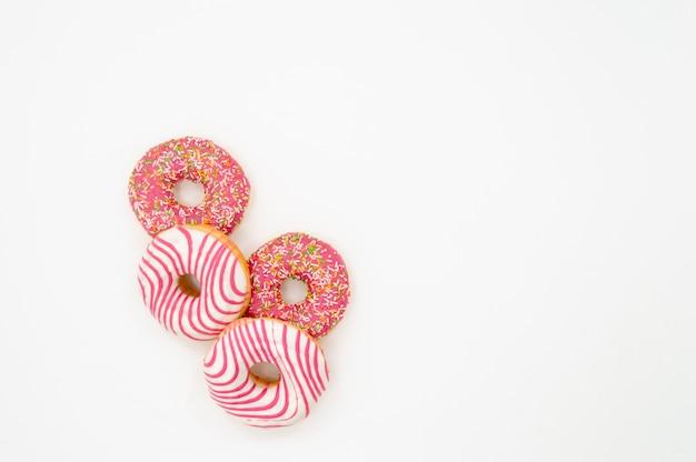 La imagen de los buñuelos helados, esmaltado rosado y asperja los buñuelos aislados en el fondo blanco