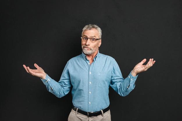 Imagen de caballero inteligente de los años 50 vistiendo atuendo profesional levantando las manos con sorpresa y expresando impotencia, aislado sobre una pared negra