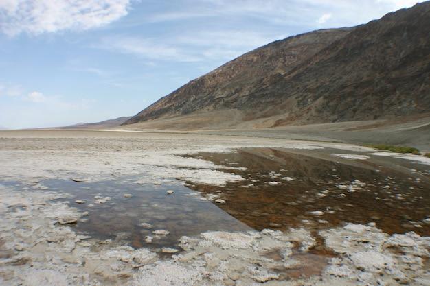 Imagen de la cara del acantilado rocoso se inclina hacia una piscina rocosa poco profunda