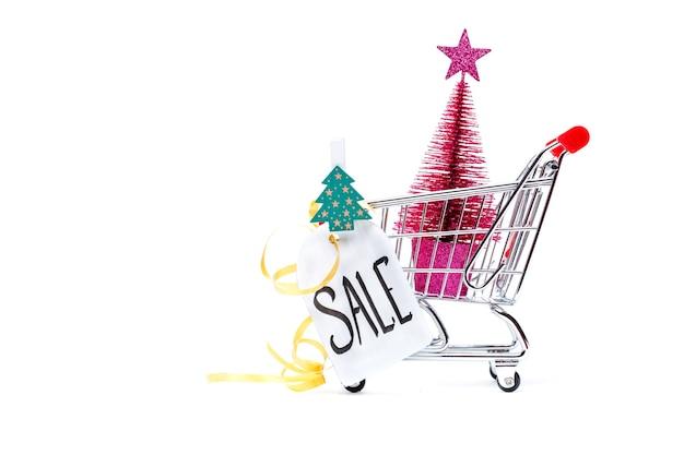 Imagen de carro con árbol de navidad, tarjeta de felicitación, cinta sobre superficie blanca vacía. lugar para el texto