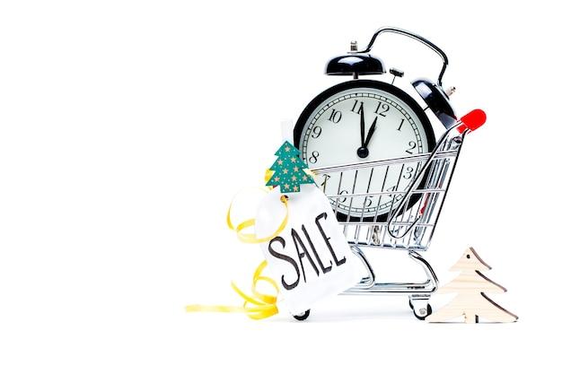 Imagen de carro con reloj despertador dorado, árbol de navidad, tarjeta de felicitación, cinta sobre superficie blanca vacía. lugar para el texto