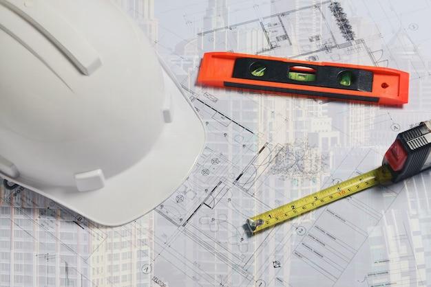 Imagen del casco de construcción blanco con nivel de medición y plano del sitio