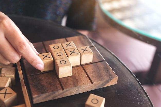 Imagen de cerca de personas que juegan al juego de madera tic tac toe o juego ox