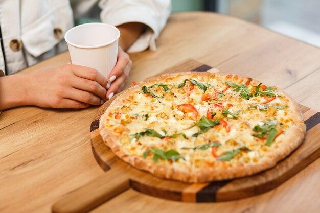 Imagen cercana de amigos compartiendo pizza tradicional italiana y bebiendo té en un café