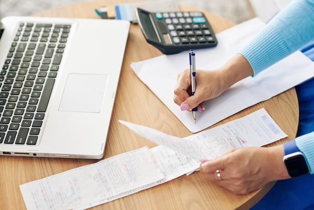 Imagen cercana de la empresaria comprobando facturas y escribiendo cifras en una hoja en blanco