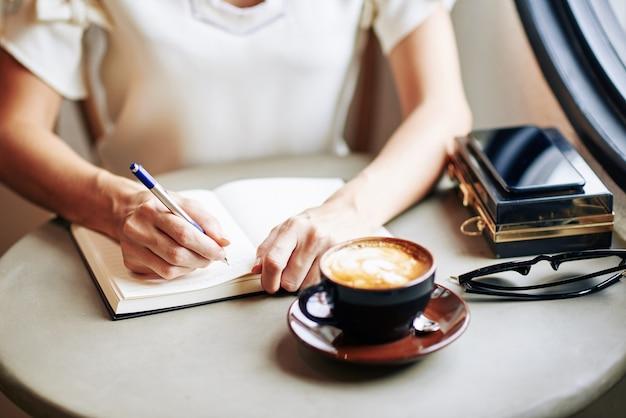 Imagen cercana de mujer bebiendo una taza de capuchino y escribiendo pensamientos e ideas en el diario de gratitud