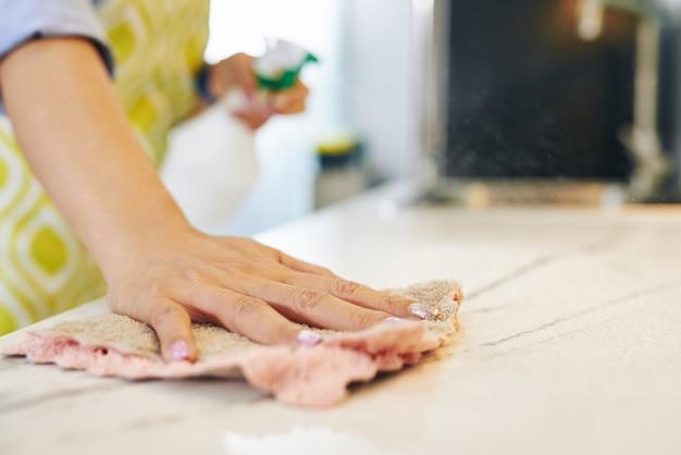 Imagen cercana de la superficie de limpieza del ama de casa en casa con spray desinfectante