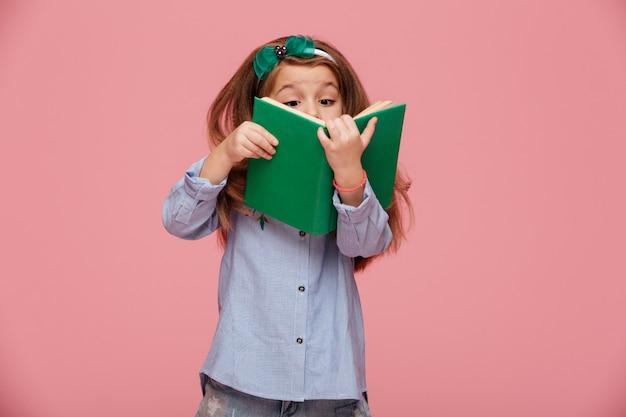 Imagen de chica divertida con cabello castaño largo leyendo un libro interesante divirtiéndose