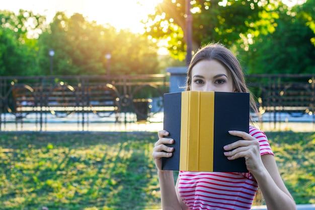 Imagen de una chica hermosa joven que se esconde detrás del libro en el parque de verano