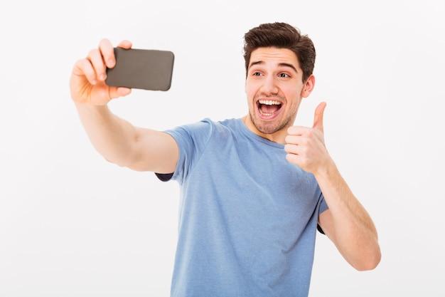 Imagen de chico feliz en estudio sonriendo y mostrando el pulgar hacia arriba mientras se fotografía en un teléfono inteligente negro, aislado sobre la pared blanca
