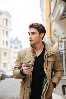 Imagen de chico guapo caminando por la calle y charlando por su teléfono al aire libre. mira a un lado.