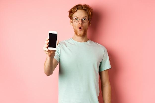 Imagen de un chico guapo con el pelo rojo, con gafas y camiseta, diciendo wow y mostrando la pantalla del teléfono inteligente, de pie contra el fondo rosa.