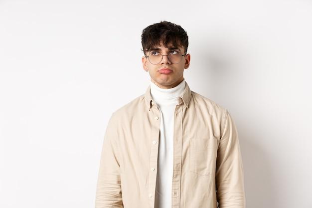 Imagen de un chico guapo triste que se siente decepcionado, frunciendo los labios y mirando el espacio vacío angustiado, de pie sobre un fondo blanco con ropa elegante y gafas
