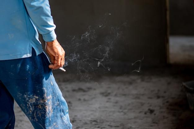 Imagen de un cigarrillo de cerca en la mano de un fumador