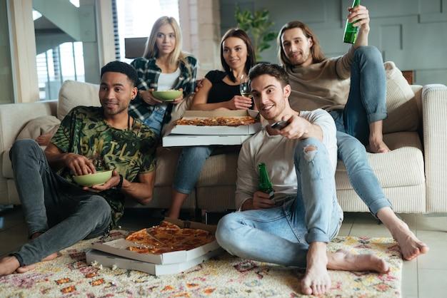 Imagen de cinco amigos mirando televisión