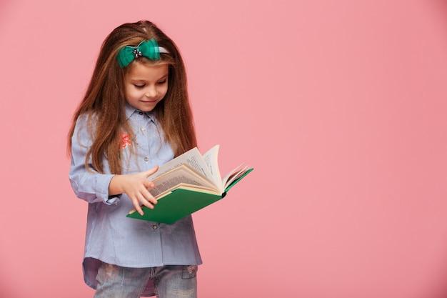 Imagen de colegiala inteligente con cabello castaño largo leyendo un libro interesante