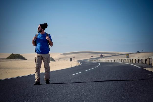 Imagen coloreada de gente hombre con mochila de viaje caminando en medio de la carretera con dunas del desierto alrededor