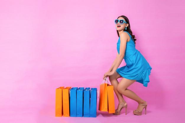Imagen completa, retrato de una muchacha bonita asiática feliz que lleva a cabo concepto que hace compras de los panieres.