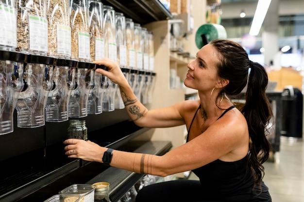 Imagen de compras de desperdicio cero, mujer comprando cereal con jarra te permite traer tu pripia bedida alcohólica